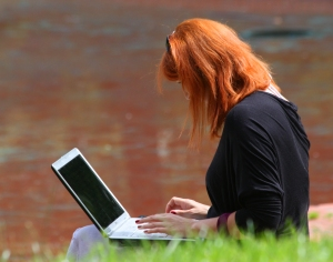 Woman working on laptop by lake